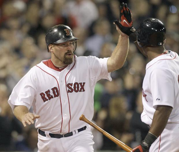 Red Sox's Kevin Youkilis is congratulated by Adrian Beltre after scoring on a passed ball in the seventh inning against the New York Yankees during the opening game of the season on Sunday, in Boston. (AP)