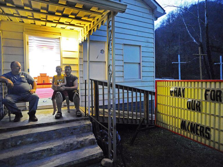 Billy Pettry, left, sits with Brandon Gray and Caden Gray, 5, on the steps of the Marsh Fork Worship Center in Eunice, W.Va., near the entrance to Massey Energy's Upper Big Branch mine. (AP) (Click to enlarge.)