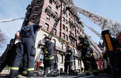 Firefighters regroup at the site of a nine-alarm fire on Beacon Street in Boston on Wednesday. Four people were rescued and taken to a hospital after a fire at the 10-story condominium building, fire officials said. (AP)