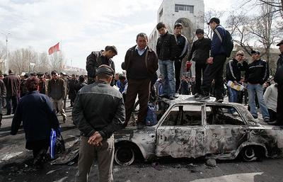 Men stand on a burned-out car in front of the Kyrgyz government headquarters in Bishkek, Kyrgyzstan on Thursday. (AP)