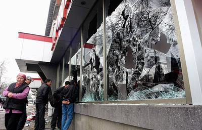 Kyrgyz people walk past windows of a shop broken by looters in Bishkek, Kyrgyzstan on Thursday. (AP)