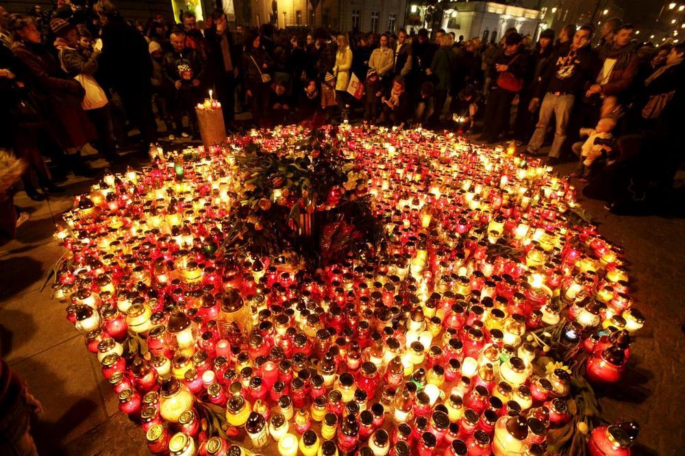 People place candles and lay flowers in front of the Presidential Palace in Warsaw, Poland, Saturday.