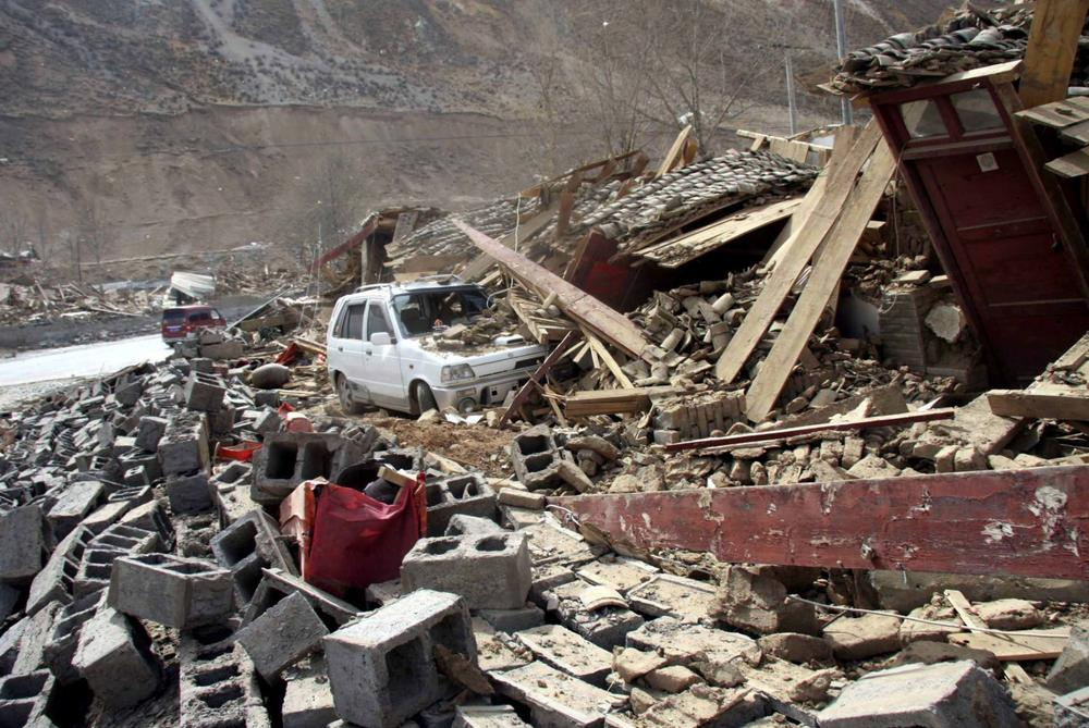A car is buried under the rubble after an earthquake in Yushu County, northwest China's Qinghai Province on Wednesday. (AP Photo/Xinhua, Ren Xiaogang)