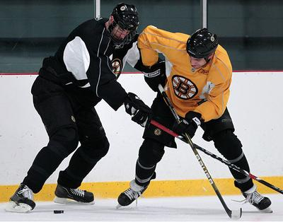 Boston Bruin defenseman Zdeno Chara, left, tries to keep teammate Milan Lucic away from the puck during a practice in Wilmington on Tuesday. The Bruins will face the Buffalo Sabres in the first round of the NHL playoffs. (AP)