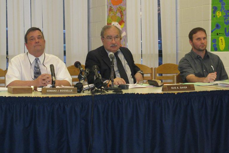 Superintendent of South Hadley Public Schools Gus Sayer, center, and school committee chairman Ed Boiselle, left, at Wednesday night's public meeting in South Hadley. (Deborah Becker/WBUR)