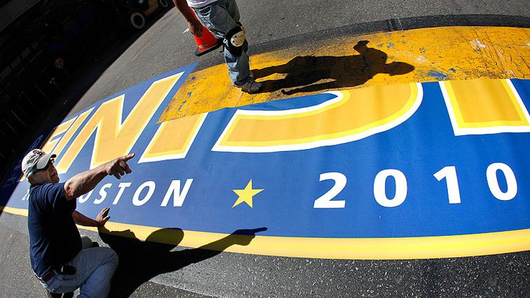 Pepi Bolognese, left, points as he and others apply the Boston Marathon finish line, made of vinyl sheeting, onto Boylston Street on Thursday. (AP)