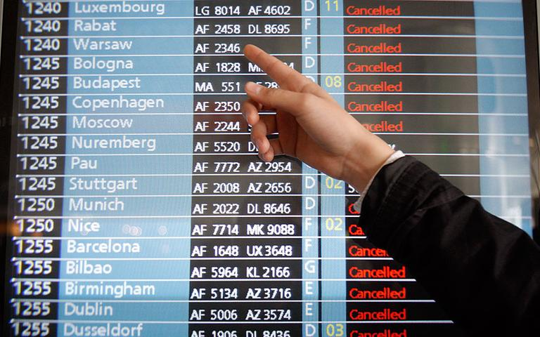 A passenger points to a flight information screen at Roissy Charles de Gaulle Airport on Friday. The Icelandic volcano that erupted Wednesday has sent an enormous cloud of microscopic ash particles across northern Europe, grounding aircraft across the continent. (AP)