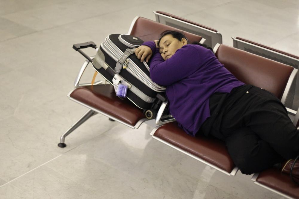 A passenger rests at Roissy Charles de Gaulle Airport, as hundreds of commercial flights across northern Europe are canceled due to a drifting plume of volcanic ash originating from Iceland, outside Paris, Sunday.(AP Photo/Thibault Camus)