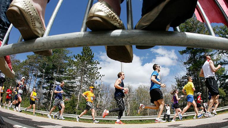 Fans stand on barricades as they cheer on runners in Wellesley during the marathon on Monday. (AP)