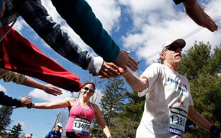 Timothy Hann, of Tempe, Arizona, right, and Lisa Plante, of Brookline, reach out to spectators near the start of the Boston Marathon in Hopkinton. (AP) (Click to enlarge)