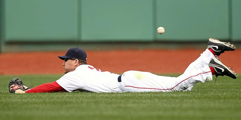 Boston Red Sox right fielder J.D. Drew has the ball get by him after making a diving attempt at a double by Tampa Bay Rays' Reid Brignac during the fourth inning at Fenway Park in Boston on Monday. (AP)