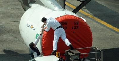 A protective cover is put on the engines of a plane grounded in Milan's Linate airport, Italy. (AP)