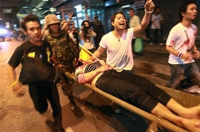 A Thai woman is rushed to an ambulance after an explosion Thursday, April 22, 2010, in Bangkok, Thailand. (AP)