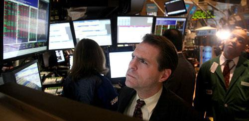 Charles Solomon, a trader with Barclay's, reviews stock information on a monitor during late trading at the New York Stock Exchange, Thursday March 18, 2010. (AP)