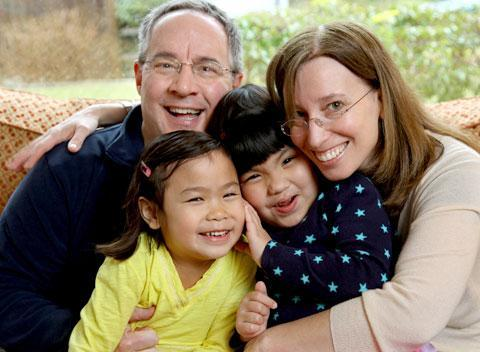 Bethany and Kevin Durkin hold their daughters Olivia, 7, left, and Lucy, 5, in their in Katonah, N.Y. home. The Durkins are part of a growing number of parents who have adopted special-needs children from China. March 13, 2010. (AP)