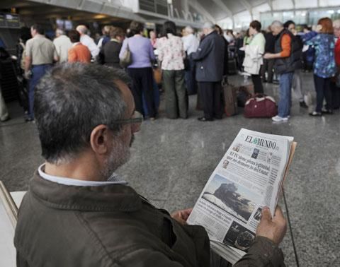 A passenger reads a Spanish newspaper showing a picture on the front page of the Icelandic volcano eruption, as he waits at Bilbao airport, April 18, 2010. The airport was closed due to a cloud of volcanic ash emanating from a volcanic eruption in Iceland. (AP)