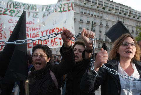 Unemployed school teachers chant slogans at an anti-government demonstration outside the Greek Parliament in Athens, Tuesday, April 27, 2010. Greece's debt crisis intensified Tuesday as its credit rating was cut to junk status. (AP)