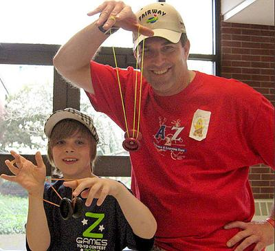 Shane O'Donnell, 10, and his dad, James, yo-yo together at the regionals. (Bill Littlefield/WBUR)