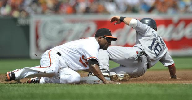 Baltimore third baseman Miguel Tejada tags out Boston's Marco Scutaro on a steal attempt during the first inning of the game Sunday in Baltimore.(AP)