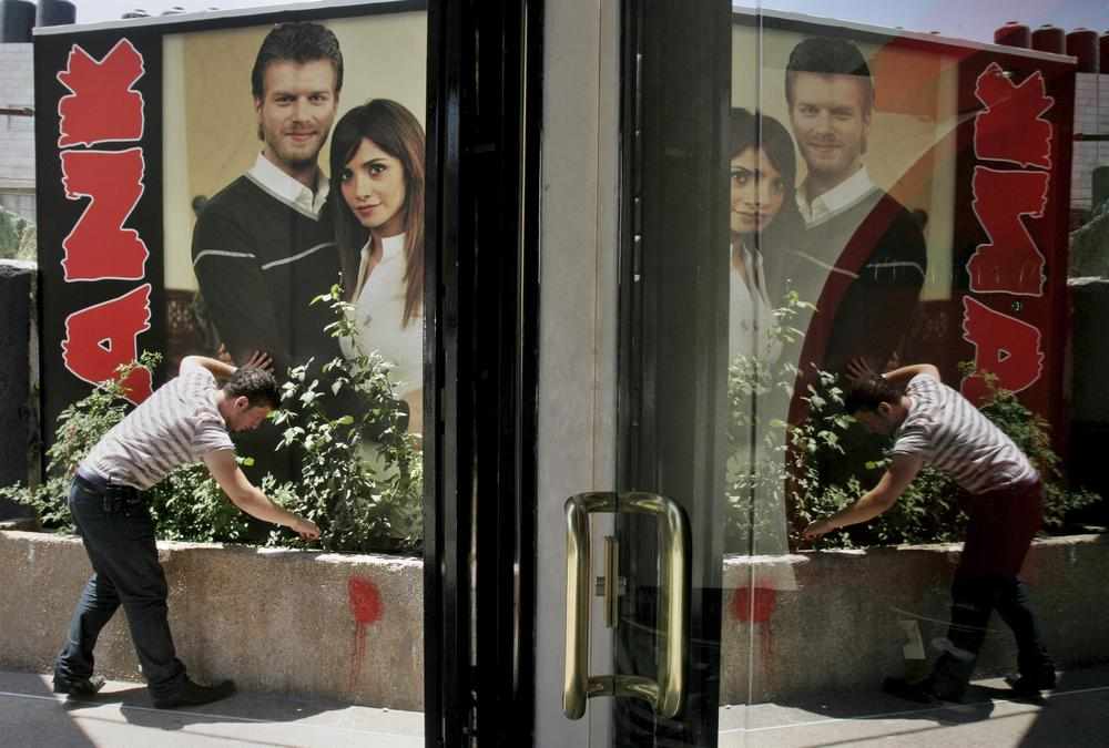 """A Palestinian vendor displays a poster depicting the lead characters of Turkish TV soap opera """"Noor"""" in front of his shop, in the West Bank town of Nablus, in 2008. (AP)"""