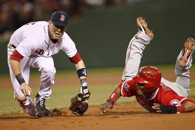 Boston second baseman Dustin Pedroia looks to throw to first to complete a double play after tagging out Los Angeles' Erick Aybar during the eighth inning of the game in Boston on Tuesday. (AP)