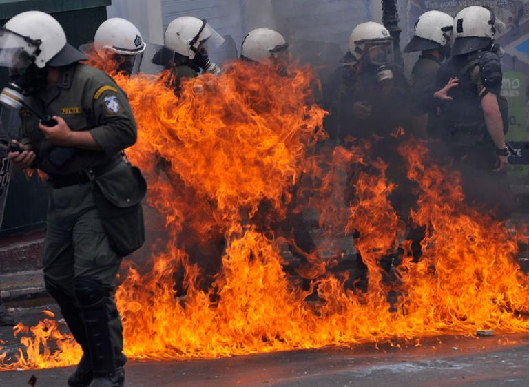 A petrol bomb explodes next to riot police in central Athens, on Wednesday. (AP) (Click to enlarge)
