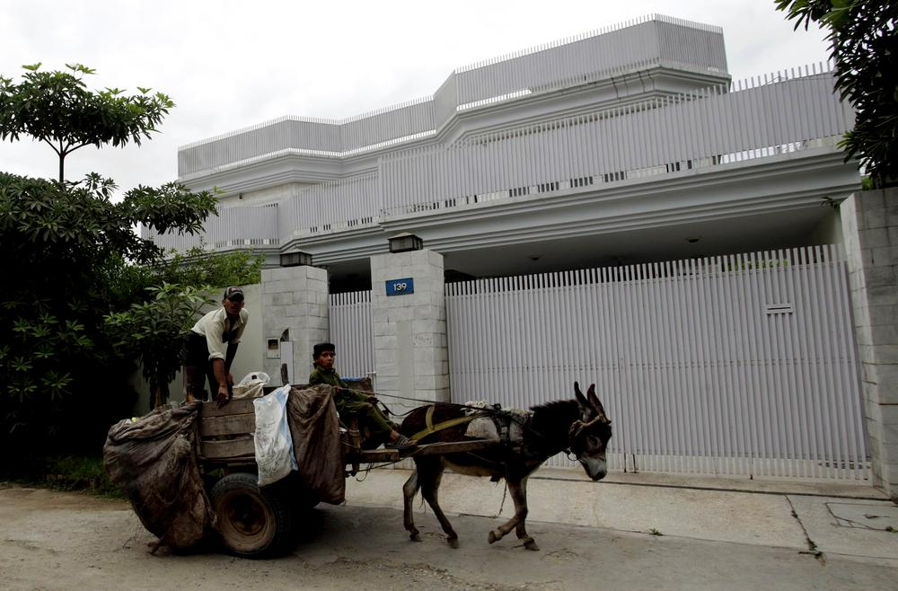 A donkey cart drives past a house, owned by the family of Times Square bombing suspect Faisal Shahzad, in Peshawar, Pakistan on Wednesday, May 5, 2010. (AP)