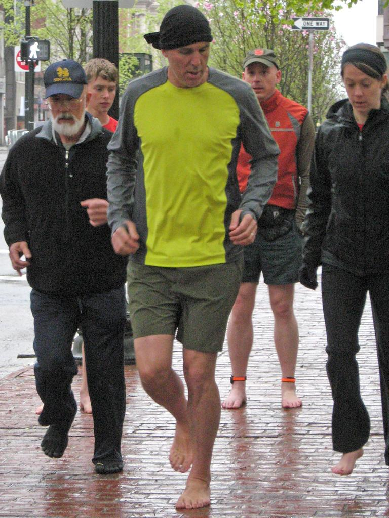 """""""Born To Run"""" author Christopher McDougall demonstrates barefoot running to a group in Boston.  (Karen Given/WBUR)"""