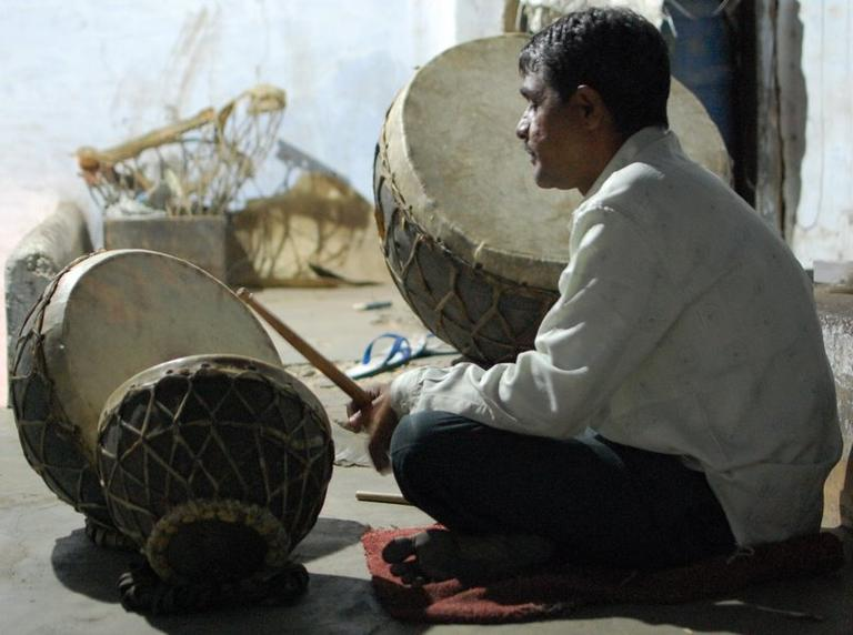 Sheru Mayuddin sits by his family's drum set in Ahmedabad, India. (Jill Ryan)