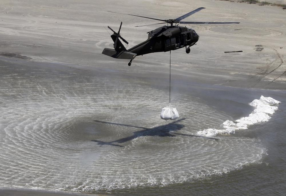 A Blackhawk helicopter prepares to drop sandbags in their efforts to dam off part of the marsh on Elmer's Island in Grand Isle, La.  (AP)