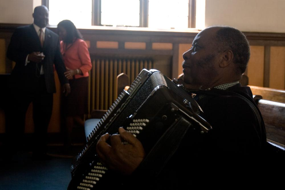 Pastor Janel Lareche, a retired minister from Haiti, practices accordion before a midday service at Philadelphie Seventh Day Aventist Church, a Haitian parish in Malden. (Jess Bidgood for WBUR)