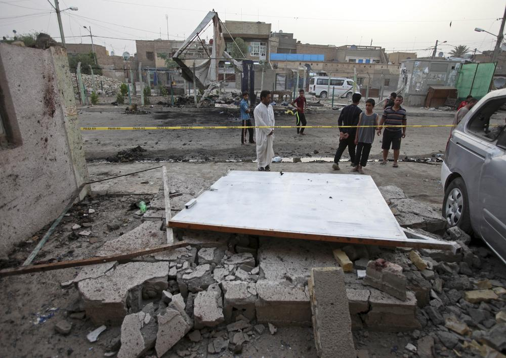 People inspect the site of a car bomb attack in Baghdad, Iraq. A car bomb ripped through a popular cafe on Wednesday evening, killing nine young people.(AP)