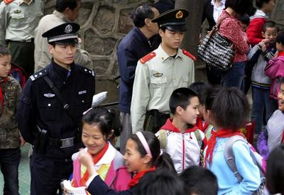 "A policeman and paramilitary police officer are now on watch over children as they leave a primary school as Chinese officials warned police will open fire on any future school attackers ""without mercy."" (AP)"