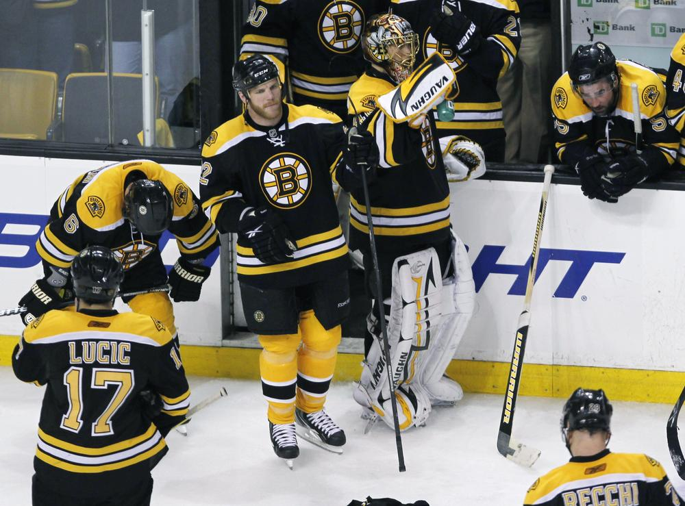 Bruins wait by their bench as the Flyers celebrate their 4-3 win in Game 7 of a second-round NHL playoff hockey series in Boston, Friday. (AP Photo/Charles Krupa)