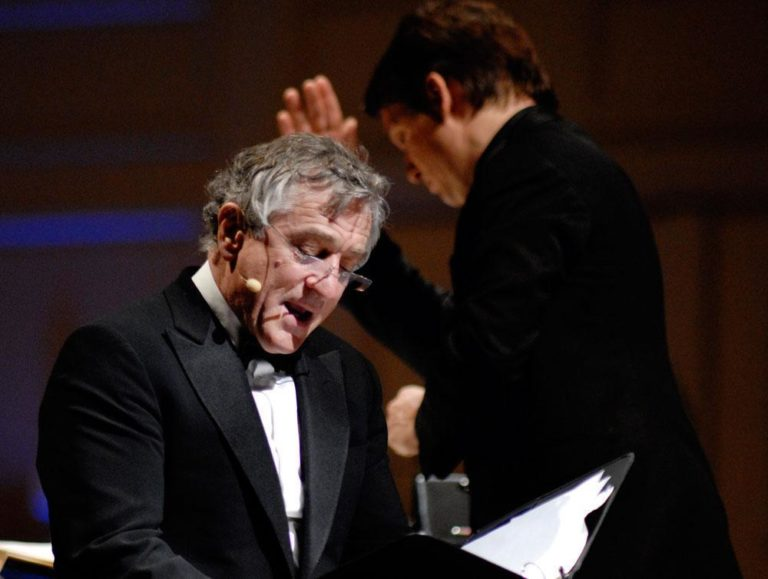 "Actor Robert De Niro, foreground, reads while the Pops' Keith Lockhart conducts during Tuesday's ""The Dream Lives On"" premiere. (Michael J. Lutch) (Click to enlarge)"