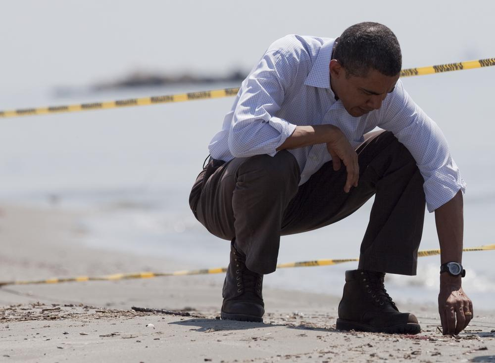"""President Obama picks up a """"tar ball"""" during a tour of areas impacted by the Gulf Coast oil spill on Friday in Port Fourchon, La. (AP)"""