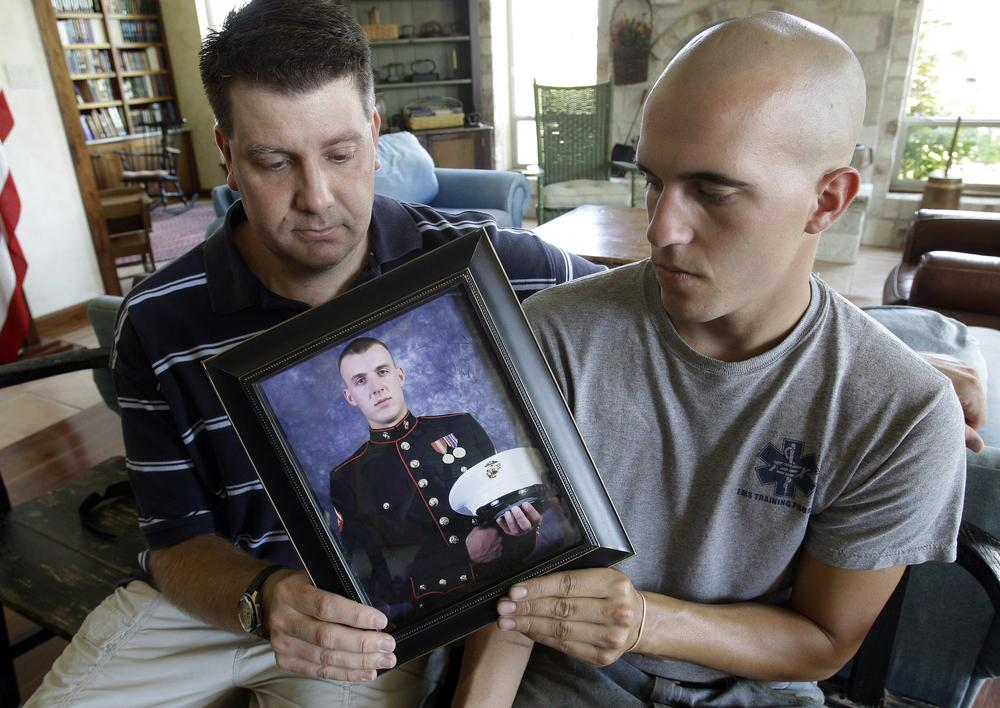Jonathan Leicht, left, and Jesse Leicht, right, pose with a photo of their brother, Marine Cpl. Jacob Leicht. (AP Photo/Eric Gay)