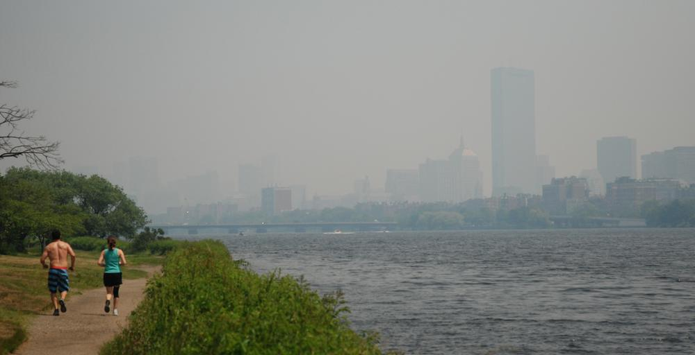 Joggers run along the Charles on Monday. Behind them, the Boston skyline is obscured by the smoky haze from wildfires in Canada. (Jess Bidgood for WBUR)