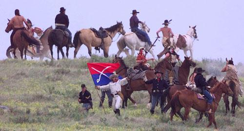 George Armstrong Custer (played by Tony Austin) stands with his flag surrounded by cavalry and warriors before his death Friday, June 26, 1998, during Custer's Last Stand Reenactment in Hardin, Mt. (AP)