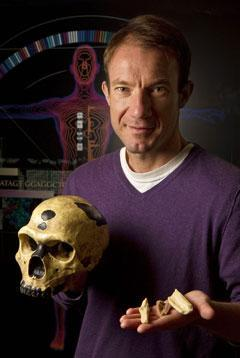 University of California Santa Cruz's Ed Green holds replicas of the bones, and a skull, from which Neanderthal DNA was extracted. (Science/AP)