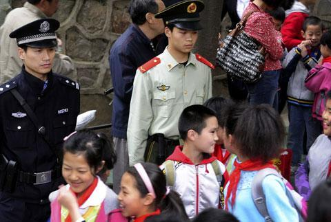 Chinese authorities watch over children as they leave a primary school in Hefei in central China's Anhui province, May 14, 2010. A string of recent assaults killed seven preschoolers and two adults last week on the outskirts of Hanzhong city. (AP)