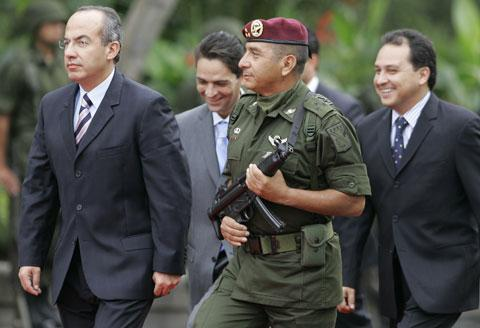 """Mexican President Felipe Calderon, left, escorted by an army honor guard and his top aides, arrives at a ceremony to commemorate the Mexican-American War and the """"Child Heroes"""" or Heroic Cadets in Mexico City, Sept. 13, 2006. (AP)"""