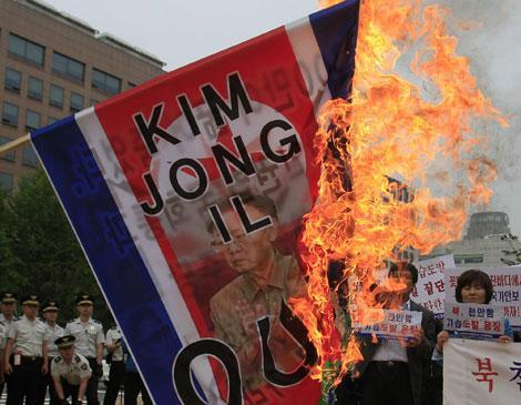 South Korean activists burn a North Korean flag with a picture of North Korean leader Kim Jong Il during a rally in South Korea, May 25, 2010. (AP)