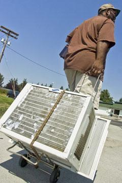 A Washington state man wheels his air conditioner out of storage during 100 degree temperatures in 2008. (AP)