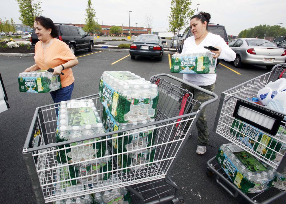 Enelcy Scott, left, and Diana Cardona load bottled water into their car outside a supermarket in Chelsea on Sunday. (AP)