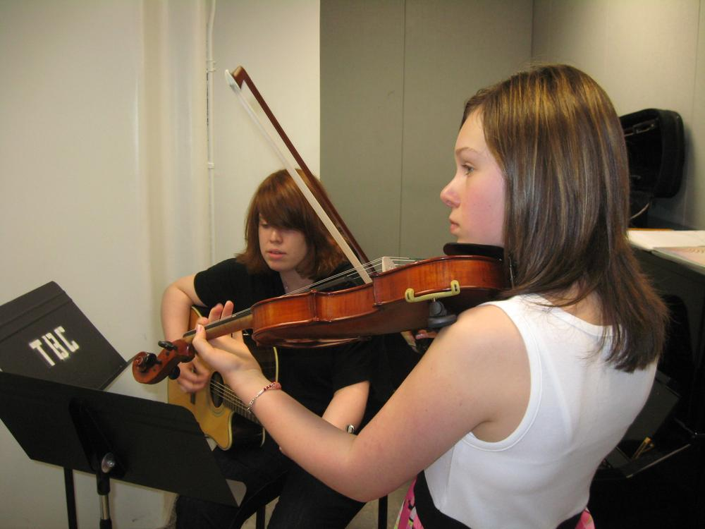 Lindsey Melo, 12, plays violin at the Boston Conservatory while accompanied on guitar by her instructor, Kristy Foye. (Sacha Pfeiffer/WBUR)