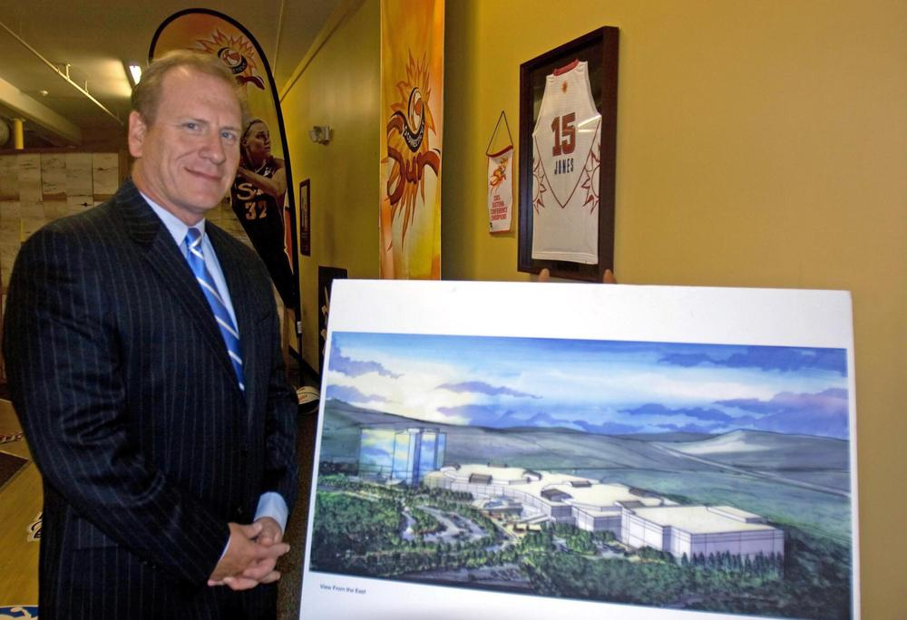 Jeff Hartmann, chief operating officer at Mohegan Sun, stands beside a rendering of a planned resort casino in Palmer. Mohegan Sun has an office in town and is already leasing the land it would build the casino on if state lawmakers approve gambling in the state and Mohegan Sun receives one of the licenses. (Lisa Tobin/WBUR)