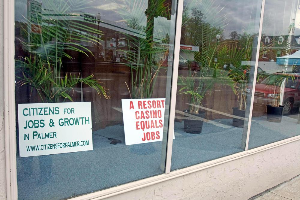There are signs like these, in a store front on Palmer's Main Street, all over town — expressing both support for and opposition to a casino in town. (Lisa Tobin/WBUR)
