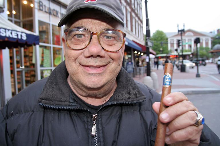 Bob Murray shows off one of his beloved cigars. (Andrew Phelps/WBUR)
