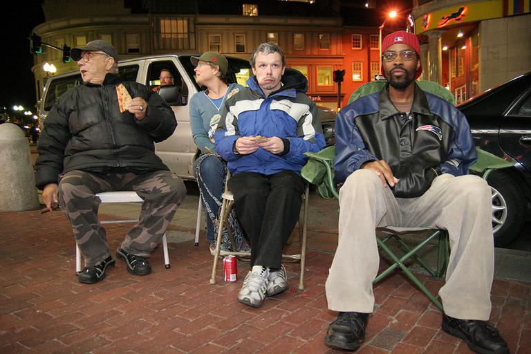 A group of regulars set up chairs outside Cardullo's in Harvard Square to watch Red Sox game through the window on the shop's flat screen TV.  (Andrew Phelps/WBUR)